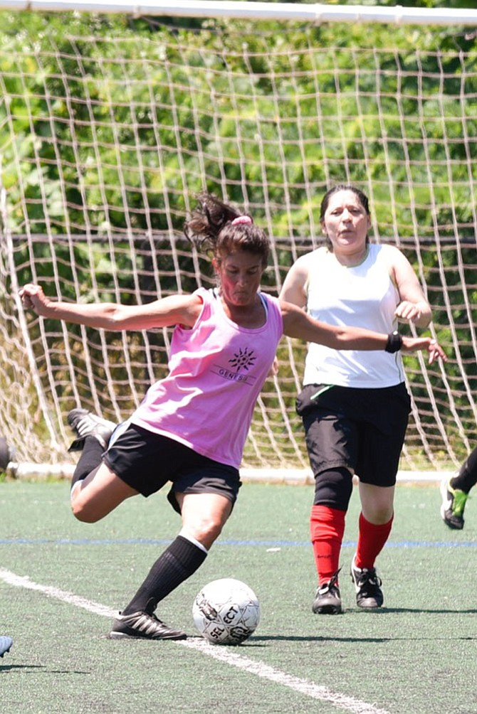 Team Genesis player, Terry Buchholz hoping to score a goal during a Fairfax Women's Soccer Association game, with Carmen Toscano of Hot Tamales in pursuit. Players from 18 to 78 have been playing in the league for more than 40 years.