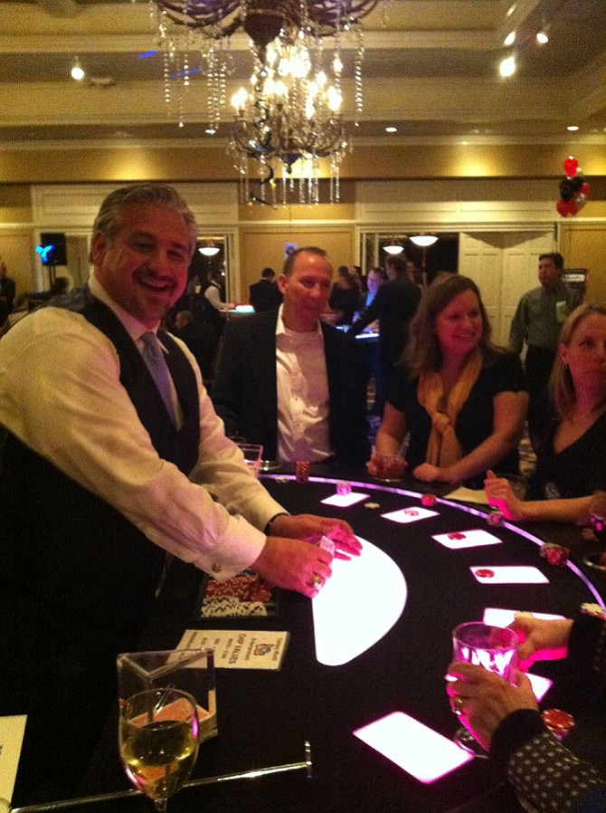 Vienna Rotary president A.J. Oskuie has fun while dealing cards at a gaming table at Casino Night.