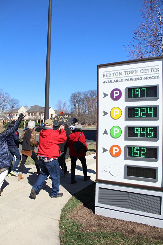 Protesters march past a Reston Town Center parking garage sign that displayed more than 1,600 vacant parking spaces in the garages—which are free on Saturdays and Sundays.