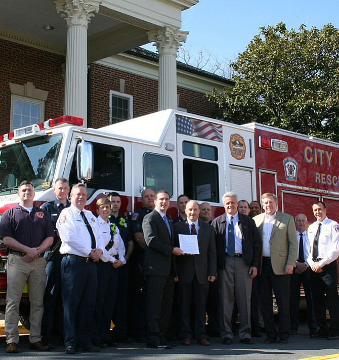 Outside City Hall, City Councilman Jon Stehle presents the letter notifying the City Fire Department about its top fire-protection rating. Also pictured are Fire Department personnel, including Chief John O'Neal (white shirt, far left) and City Manager Bob Sisson (tan jacket, on right).