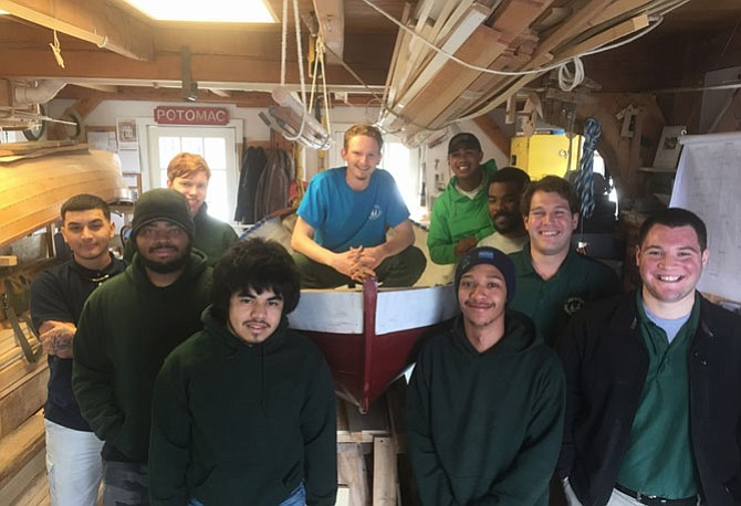 Surrounded by fellow apprentices and staff, Jay Helinksi, center, poses atop his hand crafted boat Feb. 28 to celebrate graduation from the Alexandria Seaport Foundation's apprentice program.