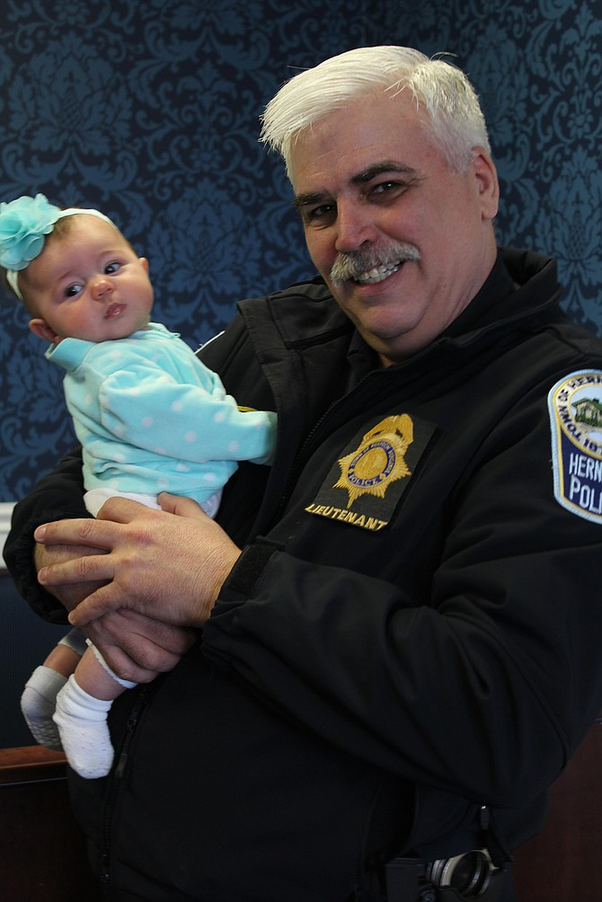 "Herndon Police Department Lt. Michael Berg scoops up 4-month-old Lila Cannell while he speaks with her mom, Shannon Cannell, during the ""Coffee with a Cop"" event at the Virginia Kitchen restaurant on Monday, March 13."