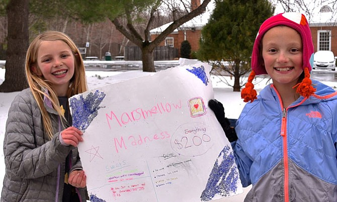 For a Good Cause —  Torie Mills and Emily Crump sell sweets to raise money for the Humane Society on Tuesday, March 14.