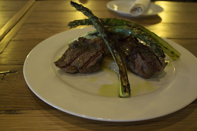 Tender lamb chops are served with potatoes and asparagus.