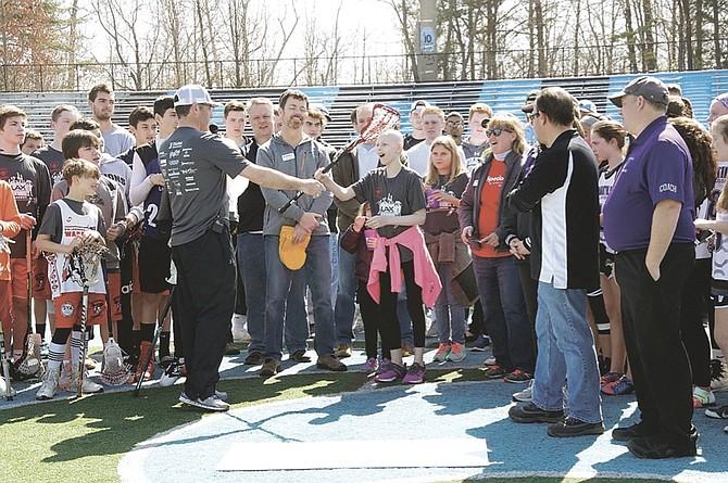 SYA lacrosse player Tatum Bulger receives a custom-made lacrosse stick.