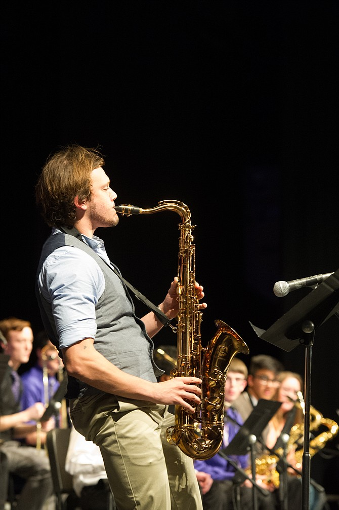 Cory Carter, Chantilly High School senior, performs a solo on the tenor sax with the Chantilly Jazz during its March 23 performance at the Chantilly Invitational Jazz Festival. In the background, seniors Jeremy Rechner, Munis Thahir and Katie Doherty look on.