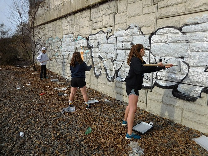 From left, volunteers Katie Harrison, Isabelle Smith and Jenna Hajji help remove graffiti from the Lorton Park & Ride lot on March 25.