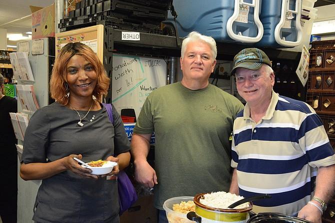 From left, Abibatu Kamara of Lorton samples venison chili from Suburban Whitetail Management's Tom Dalton of Springfield and Bob Flanagan of Fairfax Station at Lorton Community Action Center.