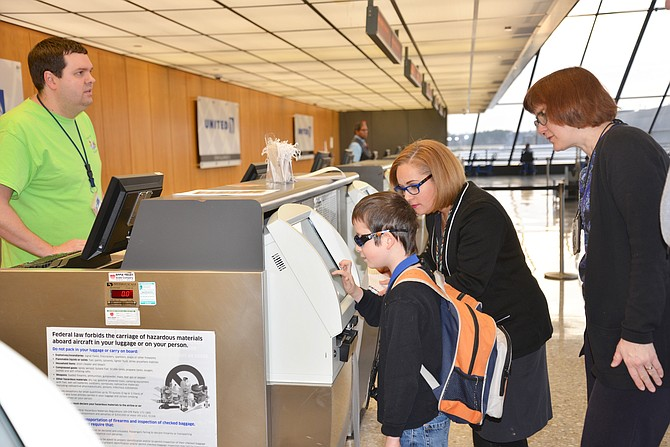 "United Airlines employees May Hester and Jeff Lattea assist Felix Reges and mom Ina Laemmerzahl of Reston to ""check-in"" to their ""Wings for All"" simulated flight travel experience at Dulles International Airport."