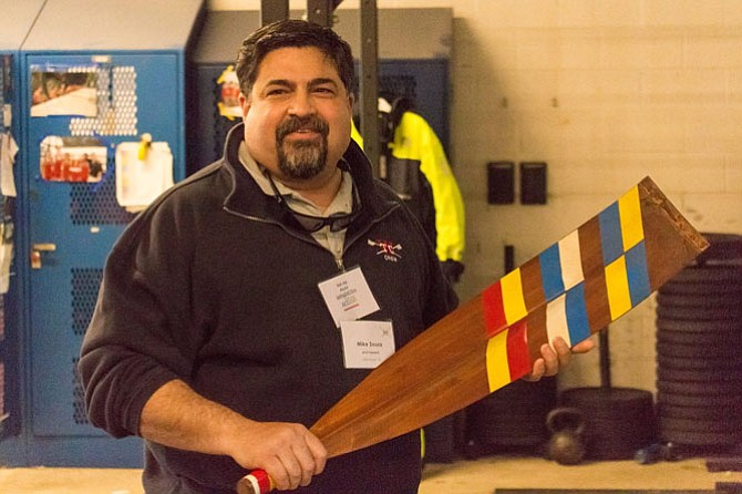 Alexandria Crew Boosters President Michael Souza holds a ceremonial oar presented by the 1971 TC Williams Crew Team.