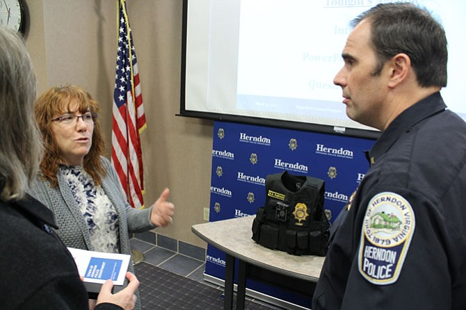 Town of Herndon resident Lorna Schmid and her husband David Boldt ask Lt. Steve Thompson of the Herndon Police Department questions about how the officers will be using the cameras. The model of camera that will be used, a Panasonic Arbitrator Body Worn Camera, was on display and will be worn by officers on their vests.