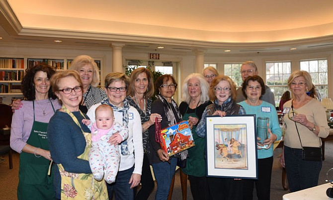 Volunteers and Shoppers, from left, are Susan Dolan, Carol Jarvis with her grandchild, Karen Meyers, Barbara Heywood, Cindy Boinis, Debra Byarn, Faith Doody, Mary Ashworth, Susie Burbage, Marianne Ryn, and Marianne Enger at St. Francis Episcopal Church's Nearly New Sale.