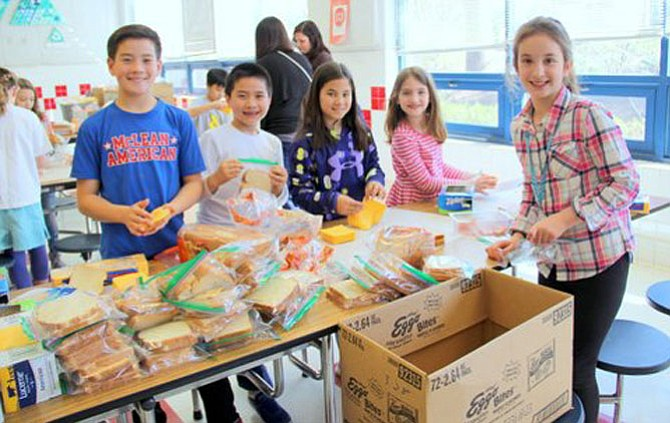 Churchill Road students Matthew Kim, Aiden Yuan, Lauren Kim, Jillian Dittamo and Meredith Cadin work together to make sandwiches for Martha's Table.