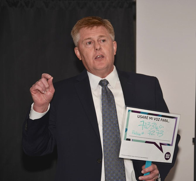 """Supervisor John Cook (R-Braddock) helps launch the """"Make a Call"""" campaign to encourage use of the 24-7 Domestic and Sexual Violence Hotline. Cook is holding the Spanish version of signage that says """"Be part of the solution, use my voice for 703-360-7273."""""""