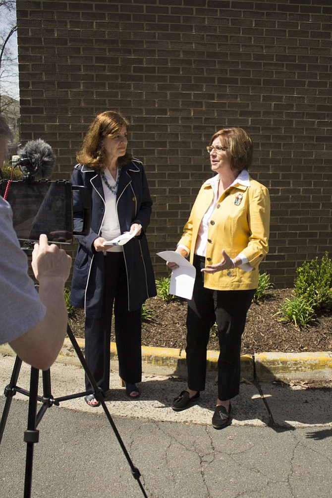 Lisa Connors, a spokesperson for the county, left, interviewed Cornerstones CEO Kerrie Wilson, right, on Facebook Live on Wednesday, April 5, outside the Embry Rucker Shelter in Reston. The video is posted on the Fairfax County Government Facebook page.