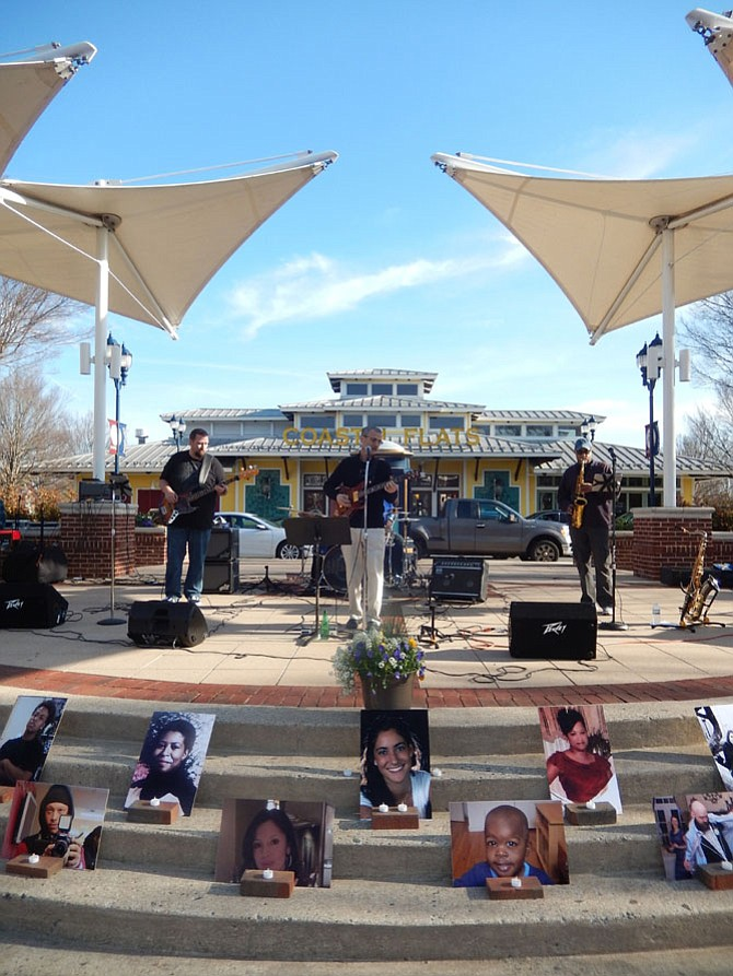 Blue Tango entertains the crowd at the Crime Victims Tribute at Fairfax Corner. In front are photos of local victims.