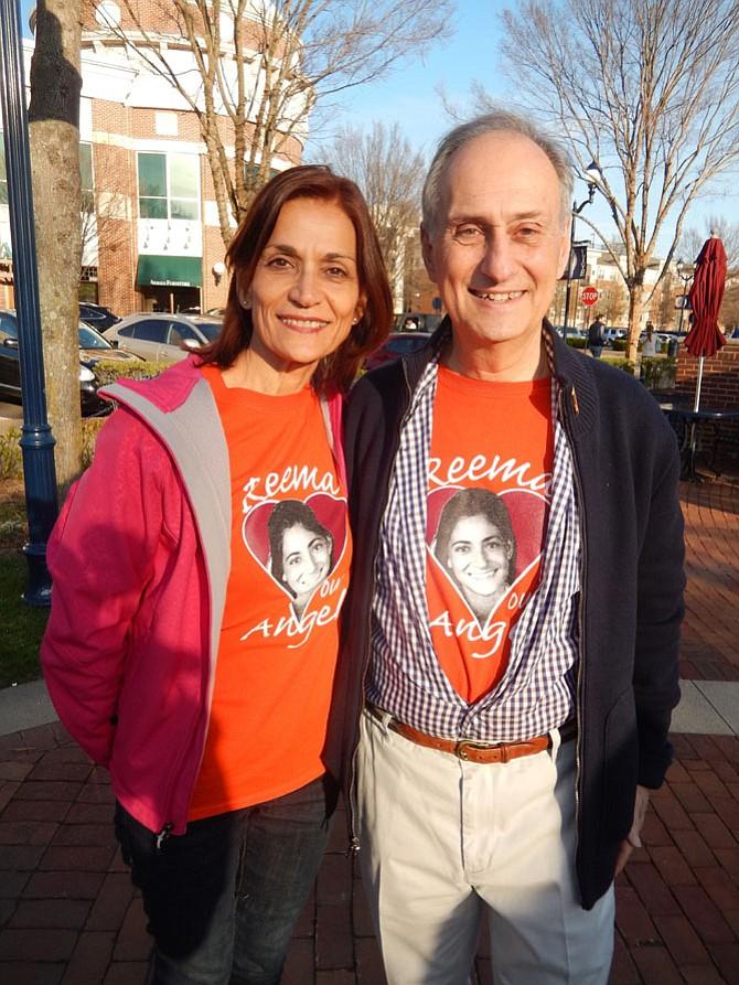 Mona and Joe Samaha wearing T-shirts imprinted with their daughter Reema's face.