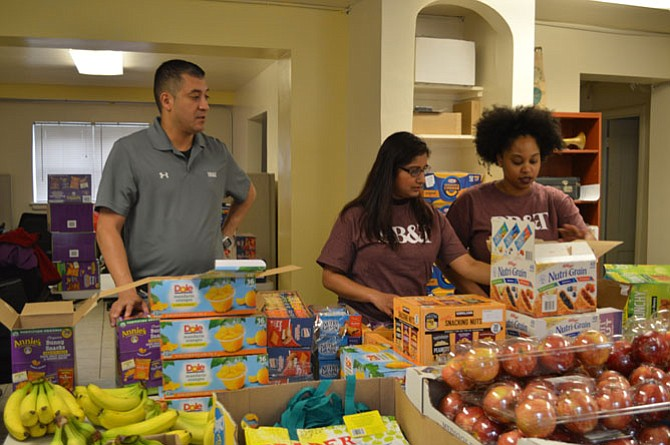 BB&T volunteers Steve Menjivar, Mythri Hanumanthaiah and Erica Lee assemble emergency food backpacks for low income and homeless children April 7 at the Community Lodgings New Brookside Learning Center as part of the BB&T Lighthouse Project.