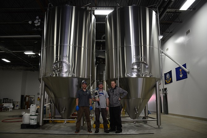 From left, Fair Winds Brewing Company's Max Courington, Charlie Buettner and Will Sonneman in front of new 120-barrel fermentation tanks.