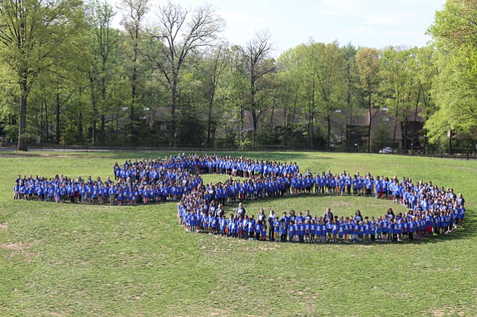 Lake Anne Elementary School students form a giant number 50 in the grass outside of the school while wearing special T-shirts the parent-teacher association bought for them on the day of the celebration.