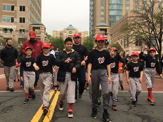 Reston-Herndon Little League (RHLL) players march in a parade in Reston Town Center on Saturday, April 22. Pictured here, AA TAG Muay Thai AL Nationals with their coach Brian Dougherty.