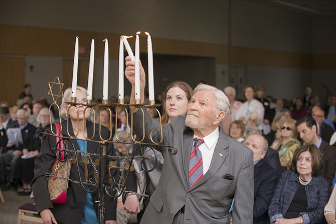 Holocaust survivor Martin Finkelstein lights a candle during the Holocaust Remembrance event at Washington Hebrew Congregation's Julia Bindeman Suburban Center.