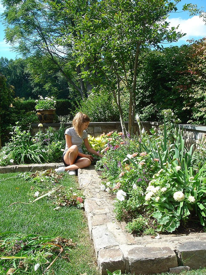 Midst the colors of spring, Celeste Funger works in the garden.