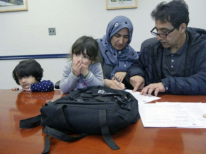 Mohammad Yaqoobi and his wife Homa sit with Natasha Jones at the Alexandria Workforce Development Center on Beauregard Street getting an orientation to the Virginia Initiative for Employment Not Welfare (VIEW) program. The family arrived from Afghanistan five months ago where Yaqoobi was a teacher and served with U.S. military forces.