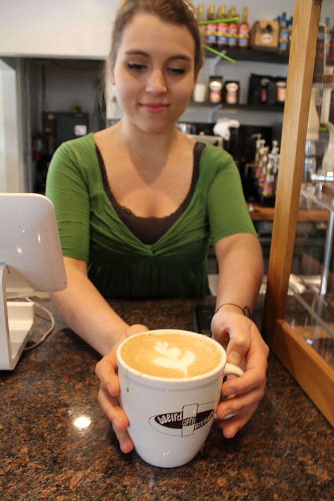 "Maddy Toland, assistant manager, serves up a latte on Wednesday, April 19. She is the Weird Brothers Coffee ""master of latte art."""