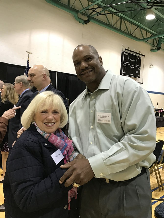 Ravin Caldwell Jr., former Washington Redskin linebacker, two-time Super Bowl champion and resident of Herndon welcomes Linda Figg, one of the 430 Outstanding Service Award Recipients, at the 33rd Annual Mayor's Volunteer Appreciation Night held Sunday, April 23.