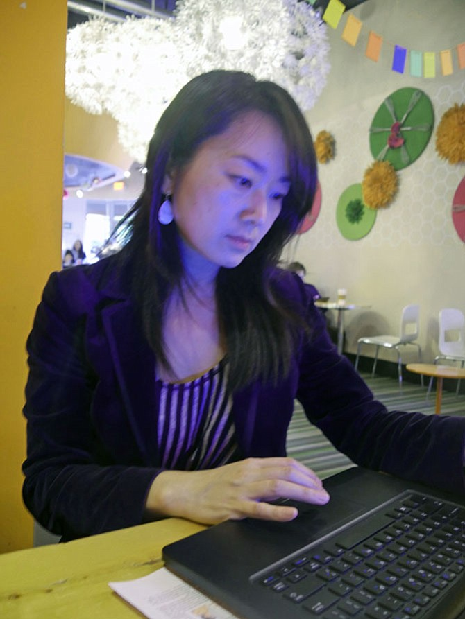 Wendy Chan, a co-founder of NOVA Friends of Refugees, pulls out her computer to illustrate the three 2017 goals of the volunteer organization: advocacy, life skills program and community events.