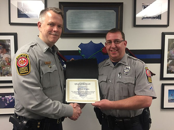 Lt. Alan Hanson (left), assistant commander of the Sully District Station, presents the Officer of the Month award to PFC Keith Allen.
