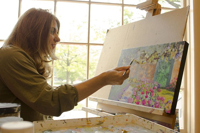 Layla Gray works on an oil painting of a Monet garden she saw during a trip to France at the Artists on the Green studio.