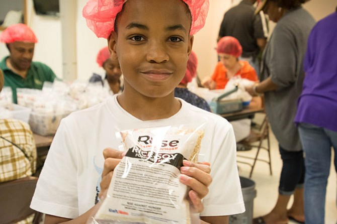 Benita Park's son, Kendall holds a finished package of Rise Against Hunger packaged meals. The volunteers met their goal of packaging 50,000 meals this year, 20,000 more meals than last year.