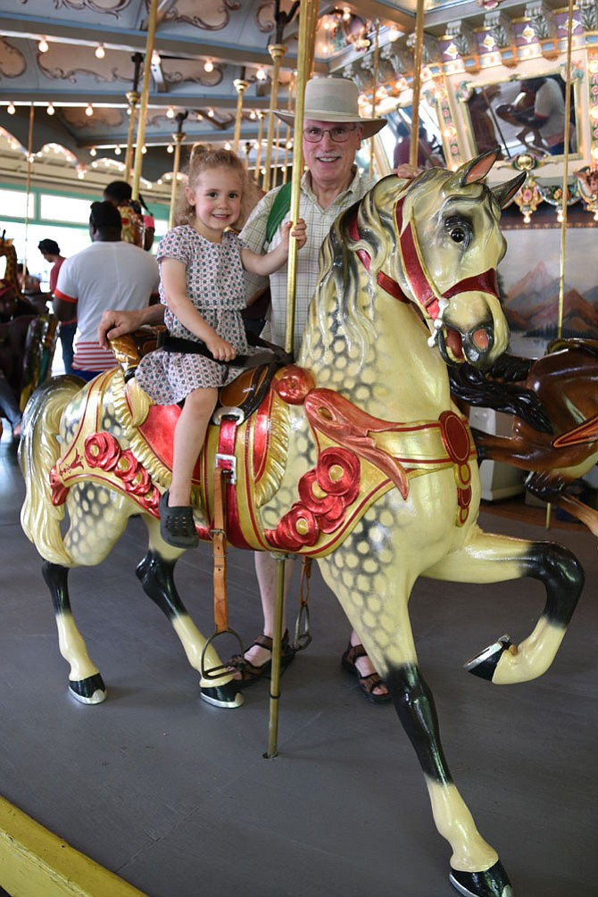 Lilly Hassinger and Rick Heuwinkel on the historic Dentzel carousel at Glen Echo Park. The carousel opened for its 97th season on Saturday, April 29.