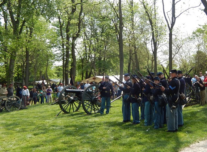 Civil War re-enactors prepare to fire a cannon.