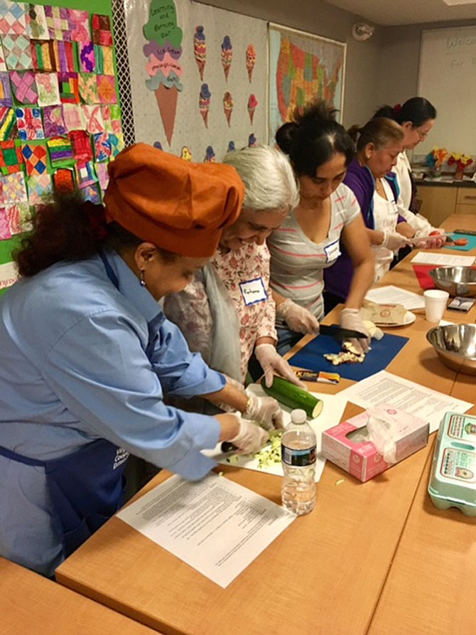 "Participants gathered around a table at Buchanan Garden Apartments May 3 to make a vegetable frittata as part of the ""Let's Get Cookin'"" program."