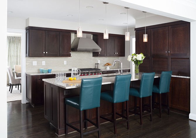 This Arlington kitchen by WINN Design + Build includes Wellborn Premier cherry wood cabinetry and custom-stained solid oak hardwood floors. Added workspace allows for easy meal prep and is ideal for entertaining.