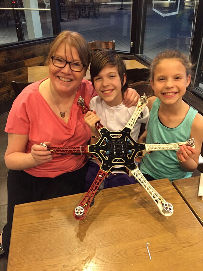 Mom Melodee Boos of Great Falls with her girls Rose and Gloria Boos (long brown hair), both 13, building a drone in April 2015. Rose and Gloria attend Cooper Middle School as seventh graders.