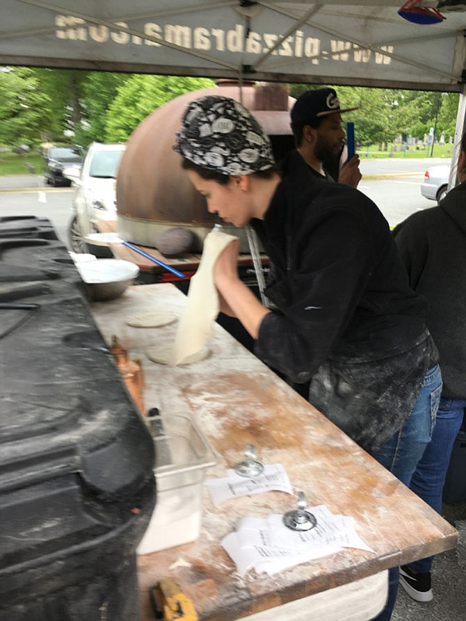 Jordan Chacon prepares pizza crust at Pizza Brama, one of several vendors at Potomac Village Farmers Market. The market is open Thursdays from 2-6:30 p.m. in the parking lot of Potomac United Methodist Church at the intersection of Falls Road and Democracy Blvd.