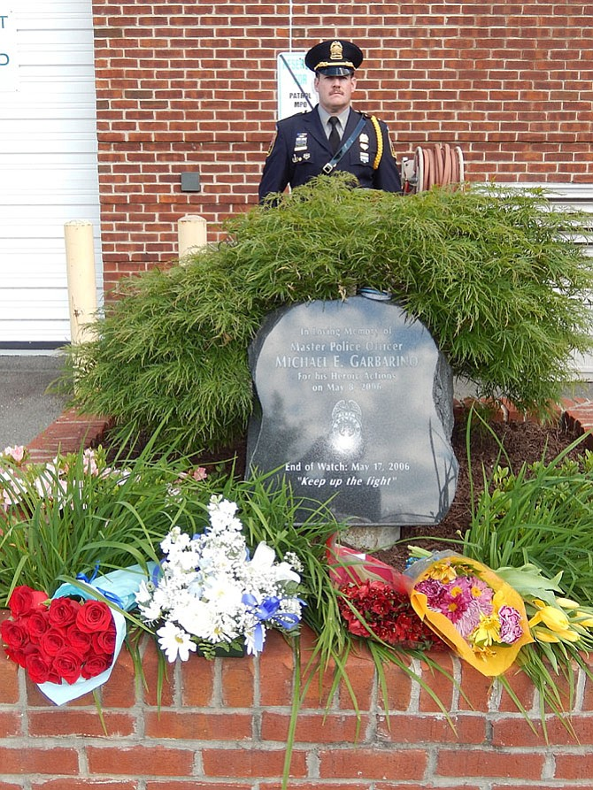 2nd Lt. Chris Cotone stands at attention behind MPO Mike Garbarino's memorial at the Sully District Police Station.