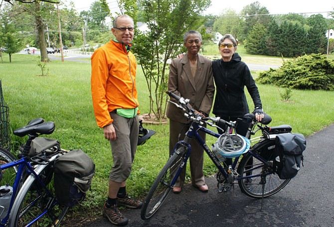 Fairfax County Supervisor Cathy Hudgins (D-Hunter Mill), center, waits with Bruce Wright and Kerie Hitt, for the Beulah Road Walkway project ribbon-cutting event to begin. Wright and Hitt demonstrated the connectivity improvements of the project by biking from Reston to the ceremony in Vienna.
