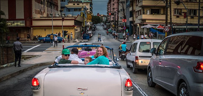 One family on the trip takes a ride in a taxi cab, a classic Chevrolet convertible.