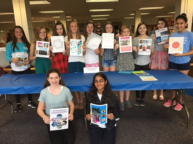 Mrs. Bovenzi's Quest students at Cooper Middle show off their personalized yearbooks, which they designed using the Adobe Creative Suite.