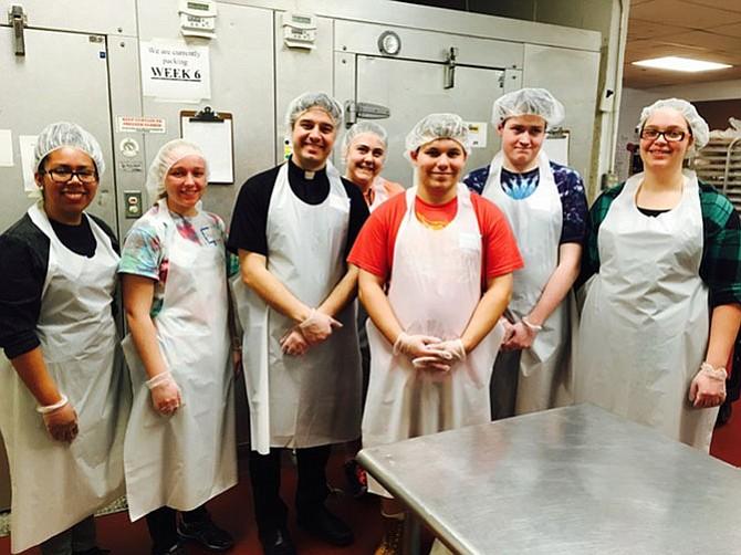 Marymount University's Margarita Hernandez, Abbie Wolf, Father Tom Yehl, Elizabeth Kasten, Andrew Boehme, Kevin Strickland and Sarah Roegner prepare to serve at a soup kitchen in Philadelphia.