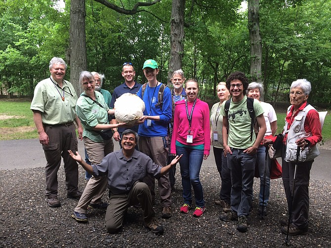 "Arlington County Natural Resources Manager Alonso Abugattas crouches on the ground while volunteers gather around a fungus that mycologist Rachel Toman and her team discovered, known as a ""puffball."""