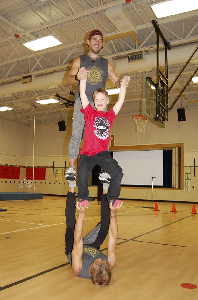 "Great Falls Elementary fourth Grader Simon Killian gets a lift during the ""American Ninja Warrior"" demonstration at the school."