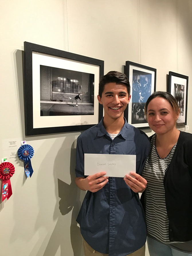 "Damion Sanchez from South County High School in Lorton, pictured with his mother,  Cynthia Sanchez, won 2nd Place and a cash award of $750 for his digital photo, ""Park's Here"" in Arts Herndon's Technology + Art = Now Competition open to students in all Fairfax County Public Schools. Damien said, ""I wanted to shoot this exact photo… it took me four takes to get the light and pose right."" Damien will attend California State Long Beach majoring in Business Management. ""Hopefully I'll become a freelance photographer after a successful business career. My money from business; my passion from photography."""