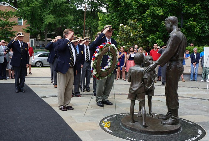 Representatives of the United States Military Academy Class of 1959 salute during the playing of Taps after placing a wreath at the Capt. Rocky Versace statue May 29 during the Memorial Day Ceremony honoring Alexandria's fallen veterans.