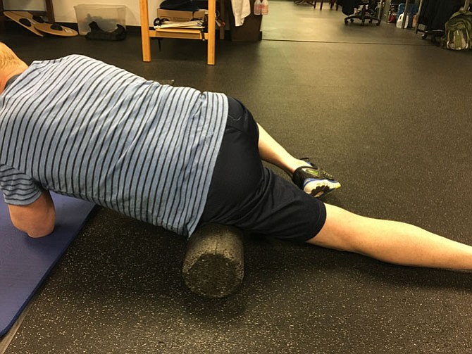 Geoff Robison of Custom Kinetics in McLean uses a foam roller to help a client recover from an injury.